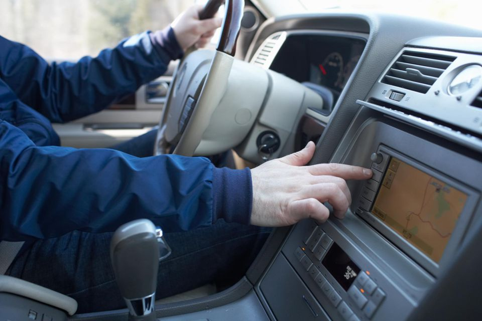 Man driving van, checking route on navigation system