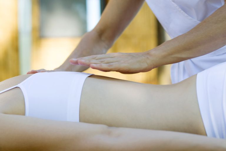 Therapist's hand hovering over patient's back