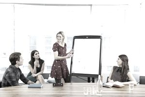 Female presenter leading a meeting, pointing to data.
