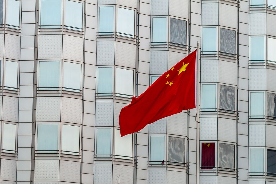 The PRC flag flying in front of an embassy.