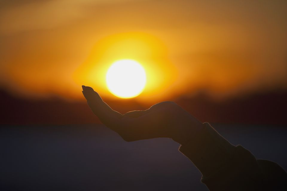 Person cupping hand under sun