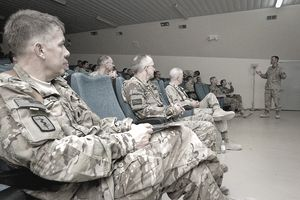 members of the military listening to a speaker