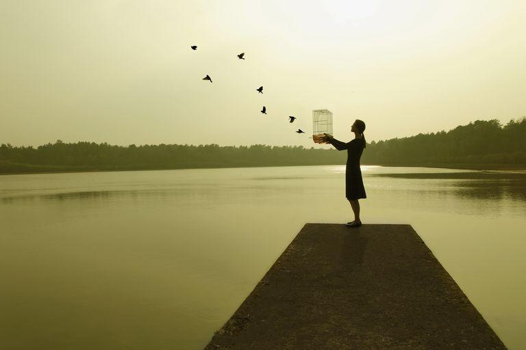 una mujer libera pájaros de su jaula