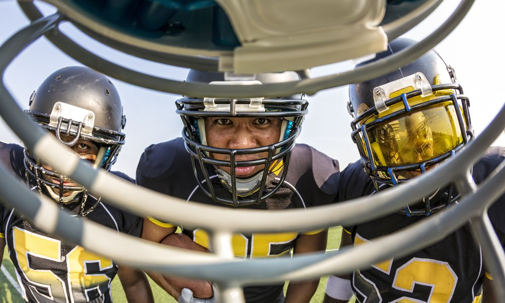 Football players looking at a player through a mask.