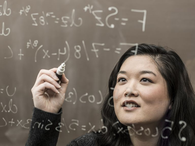 Korean student solving formula on glass wall