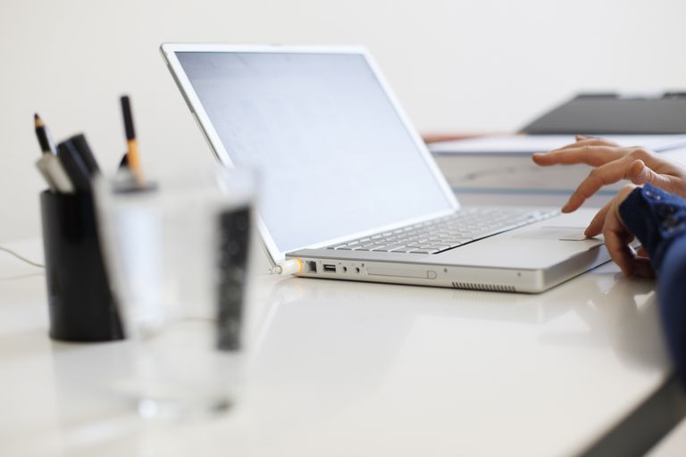 Close up of woman's hands using laptop at home