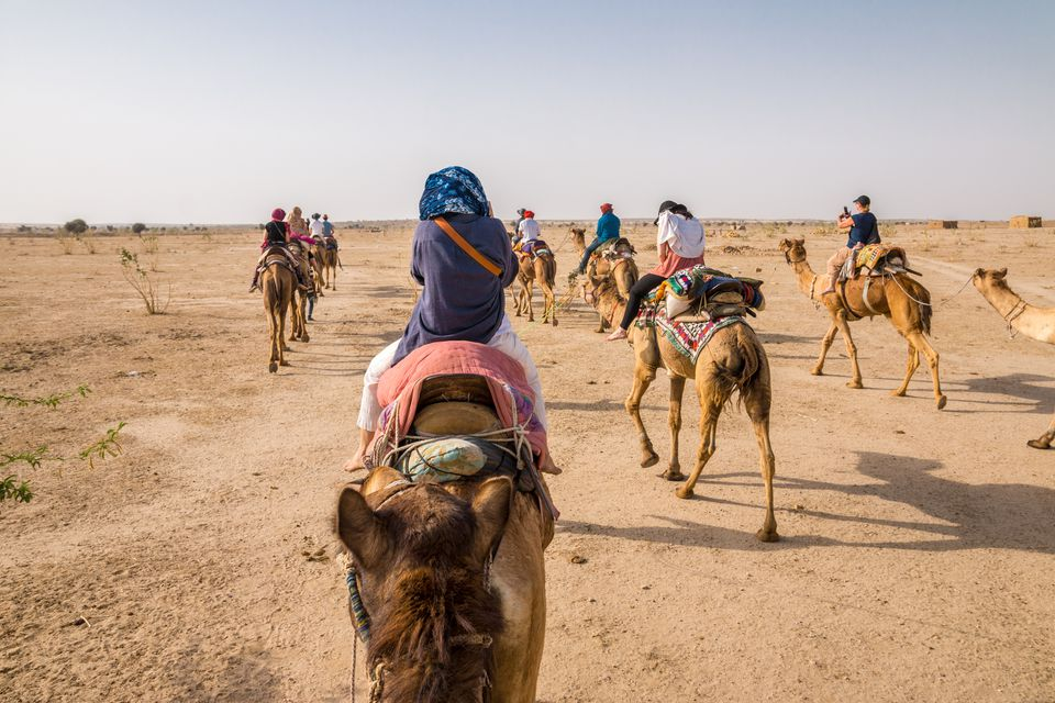 Tourists Riding Camel through the Thar Desert near Jaisalmer, Rajasthan, India