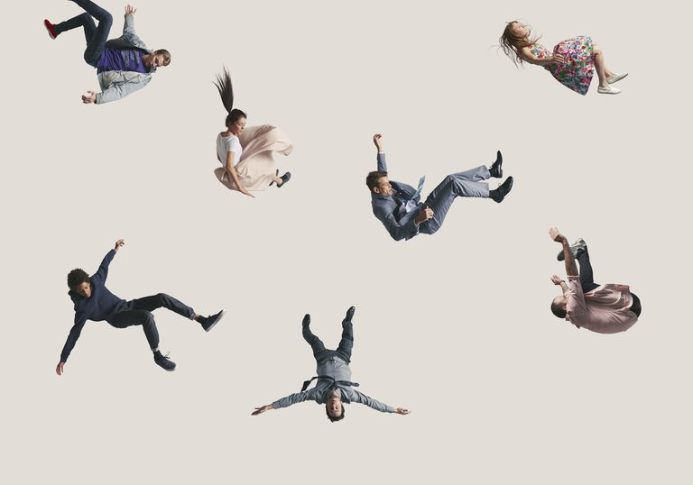 People captured in mid air, while jumping on trampoline in big studio.