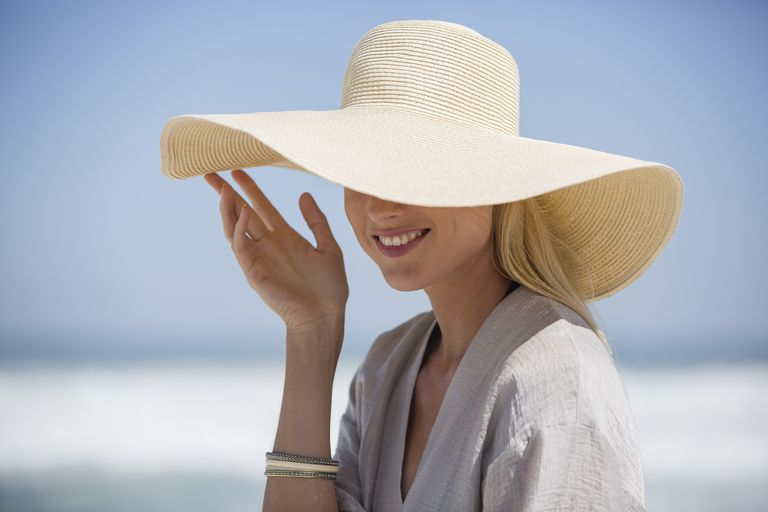 woman covering hair with sun hat