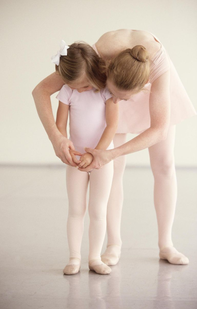 Ballet instructor helping girl at class