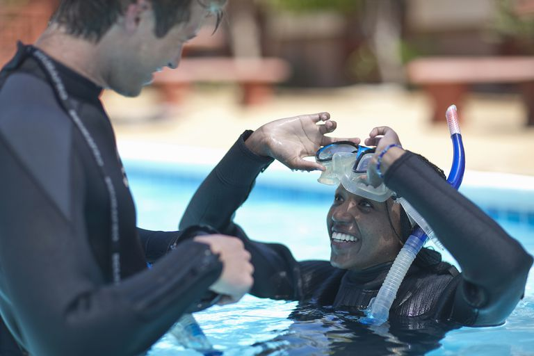 Scuba diving instructor with female pupil in swimming pool