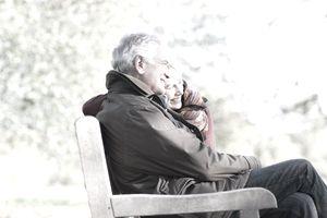 Senior couple hugging in park bench
