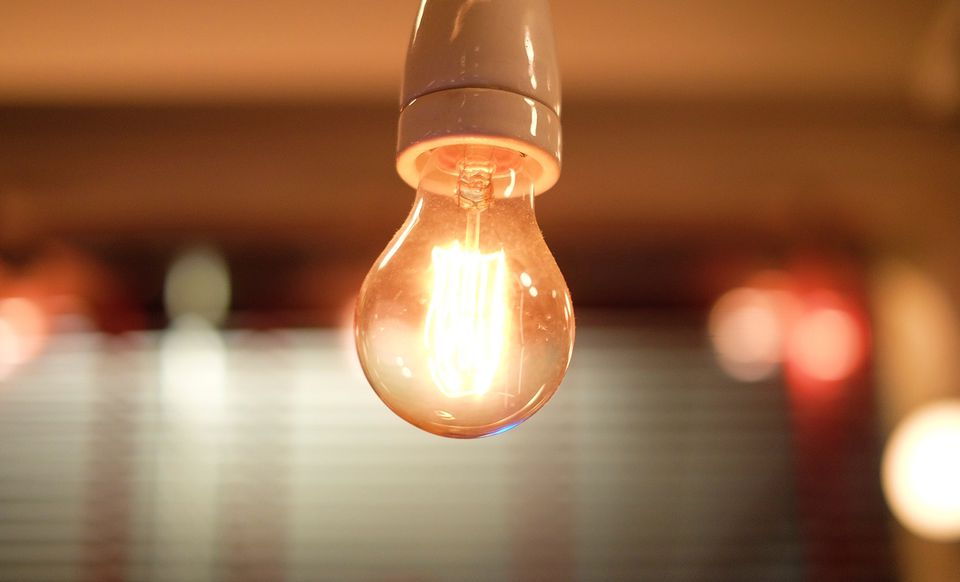 Close-Up Of Illuminated Light Bulb In Room
