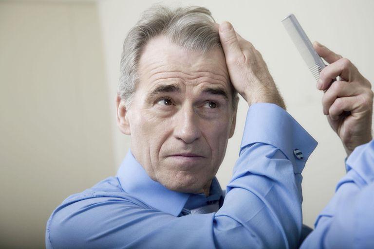 Senior man combing his hair