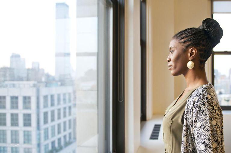 Female Office Employee Gazing out of Office Window