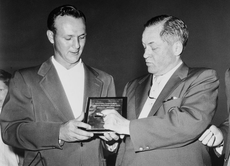 Arnold Palmer, left, young pro from Latrobe, Pa. is presented with the championship plaque by Bobby Jones, president of Augusta National Golf Club, at the 1958 Masters