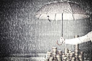 a man holding an umbrella over a stack of coins