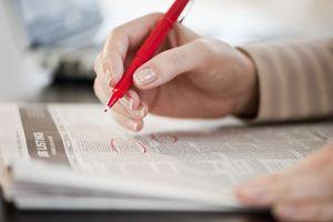 Hands circling job listings in newspaper