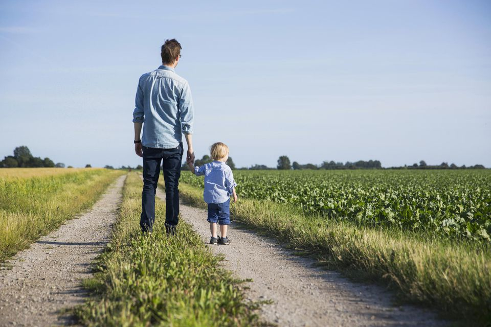 Rear view of father and son standing on dirt road at field