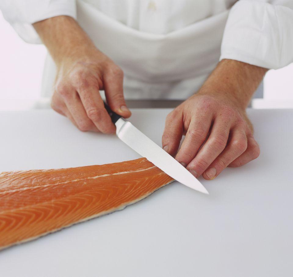 chef slicing skin off salmon