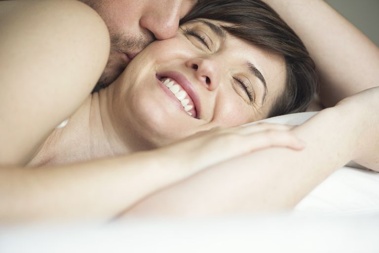 man kissing smiling woman on cheek in bed