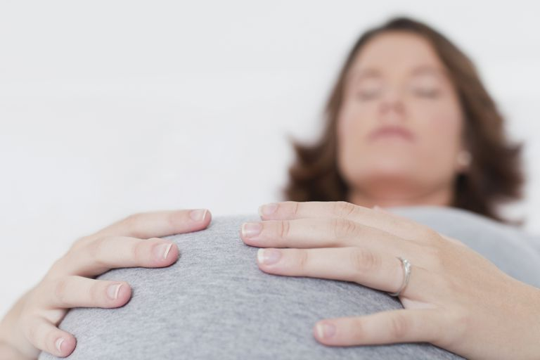 Sleeping woman holding pregnant belly