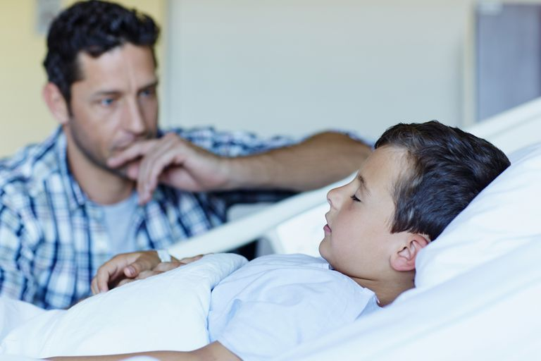 Tensed father with ill son sleeping in hospital