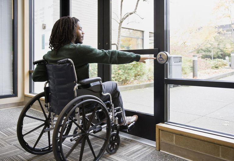 African man in wheelchair using automatic door