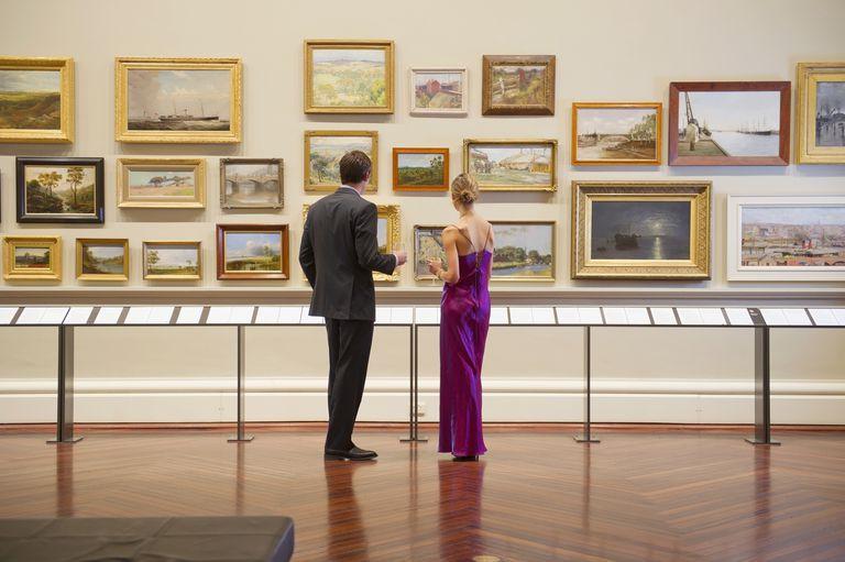 Caucasian couple in evening wear admiring art in museum