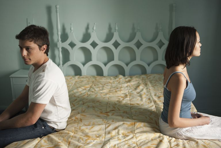 Couple sitting on separate sides of bed, both looking away