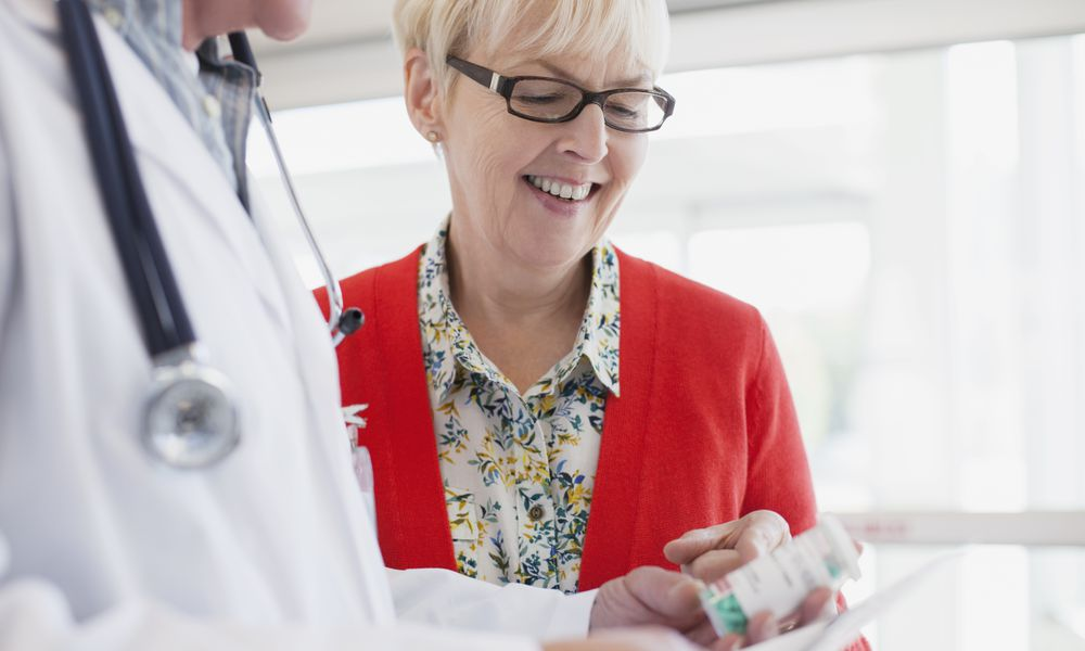 doctor reviewing prescription with senior woman