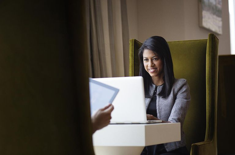 Woman Working on Laptop Opposite her Friend