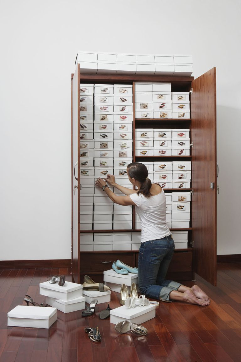 Young woman organising stacks of shoeboxes in wardrobe in an OCD fashion