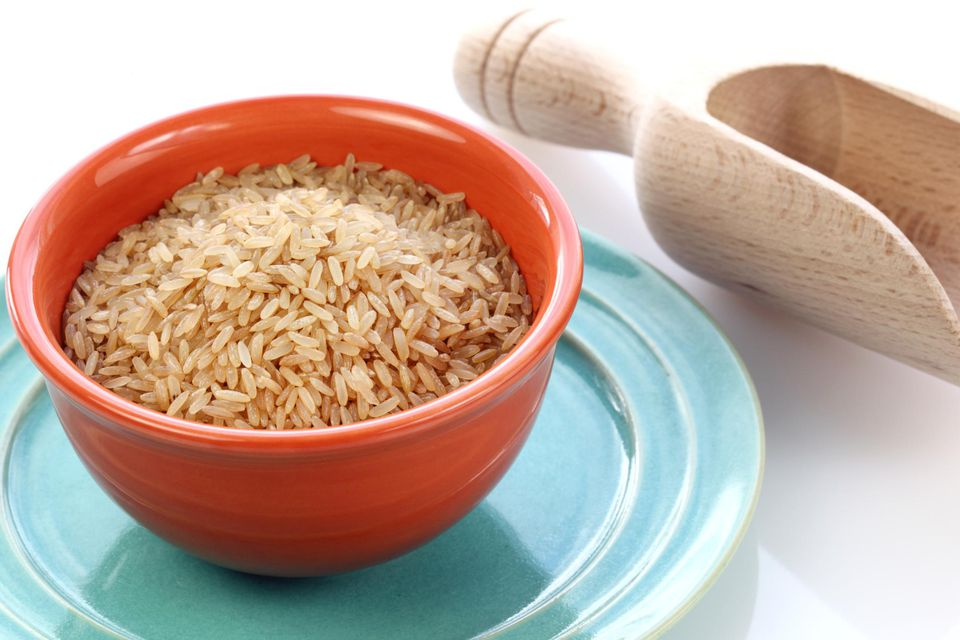 Brown rice in bowl with wooden scoop