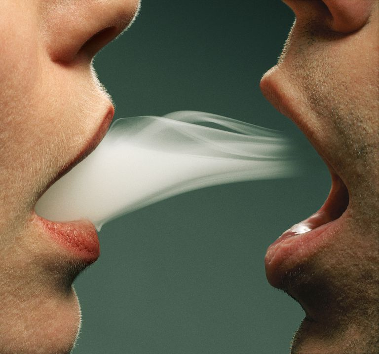 Man exhaling smoke into woman's mouth