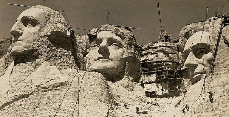 Mount Rushmore under construction, with Roosevelt's face covered with scaffolding.