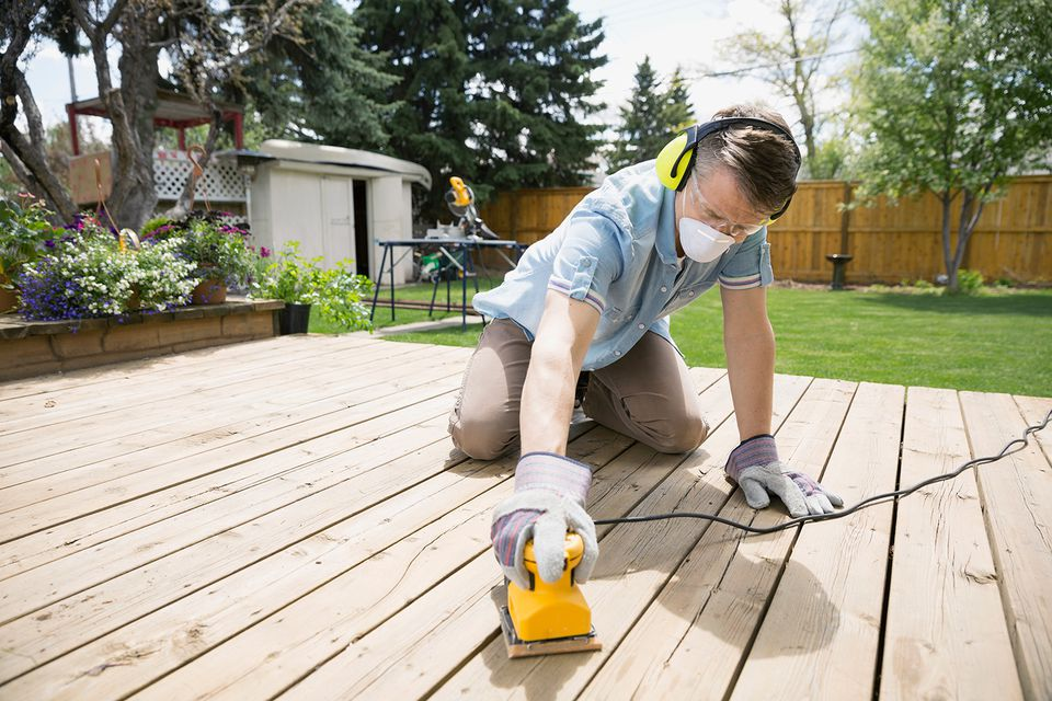 Man sanding backyard deck