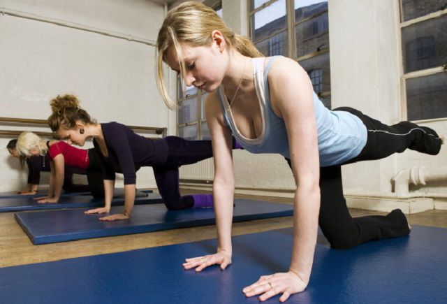 Women in exercise class practicing Pilates table legs routine