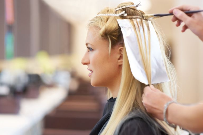 Woman getting her hair highlighted at a salon