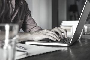 Man typing on laptop computer, cropped