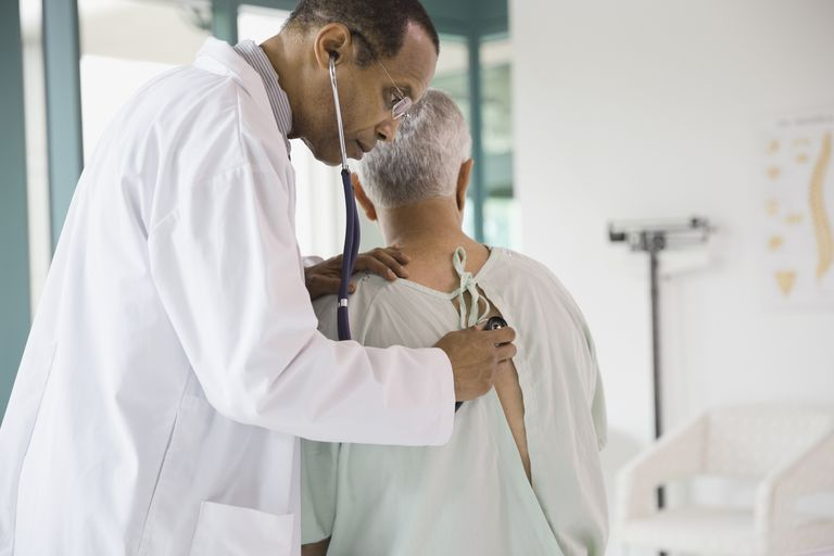 Male doctor checking senior patient with stethoscope