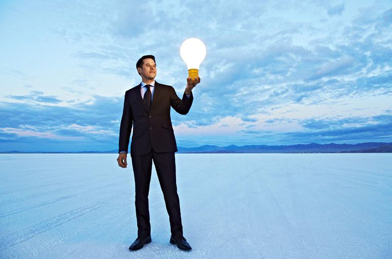 Businessman holding giant lightbulb in desert.