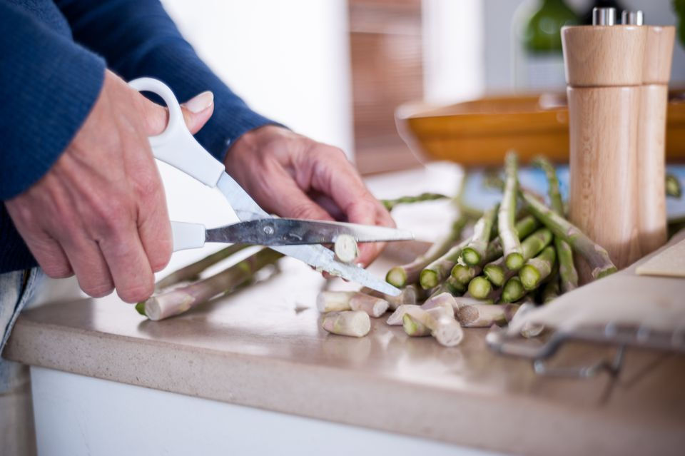 Using scissors to cut asparagus
