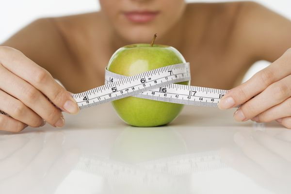 Woman measuring apple with measuring tape