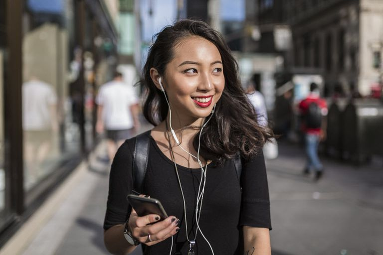 Smiling Asian woman listening to streaming music on her phone in a crowded city.