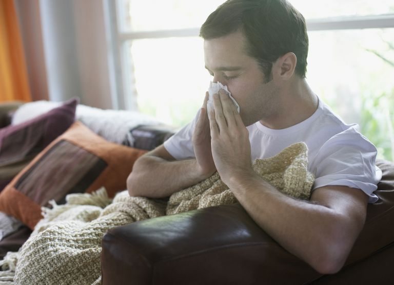 Man blowing nose at home on couch