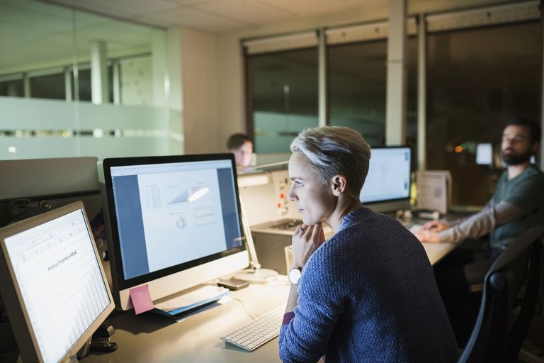 Businesswoman working late at computers in office