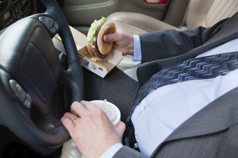 businessman eating fast food while driving car