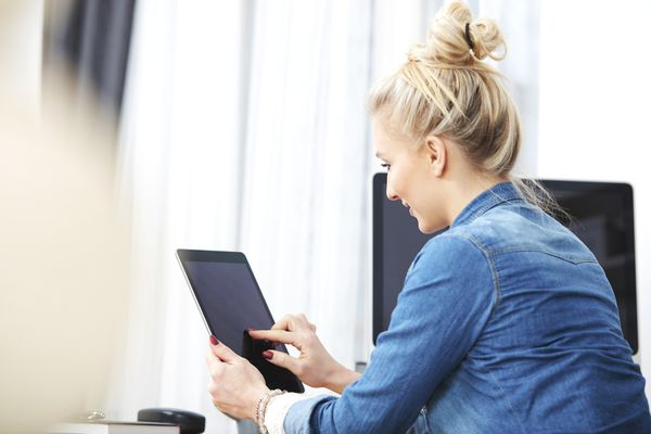 Blond woman sitting at desk using digital tablet