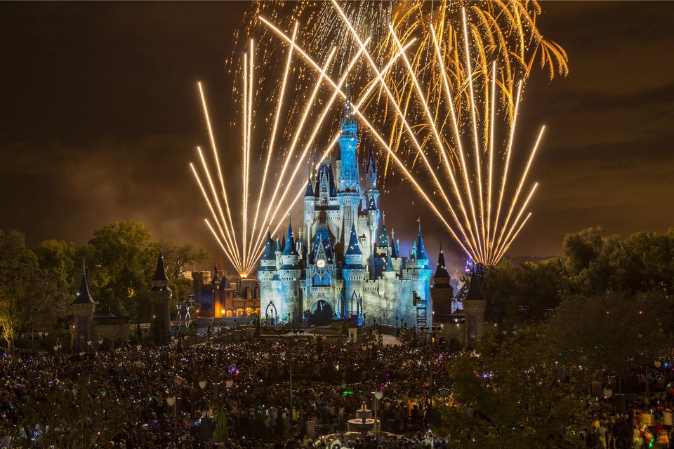 White and gold fireworks explode over a blue and white Cinderella Castle at Disney's Magic Kingdom.